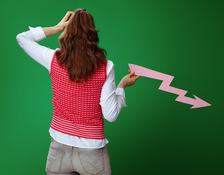 Seen from behind fit learner woman in grey jeans and pink sleeveless shirt with falling down graphics arrow isolated on chalkboard green. Economy study Stok Fotoğraf