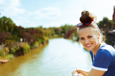 Portrait of smiling trendy traveller woman in blue t-shirt on river boat having river voyage.