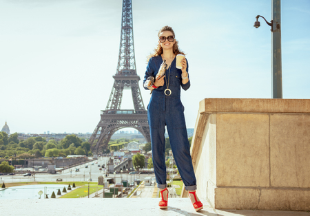 Full length portrait of happy trendy woman in blue jeans overall with coffee cup and two baguettes not far from Eiffel tower in Paris, France.