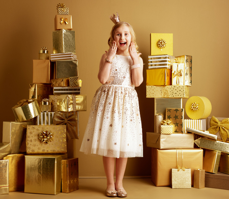 Full length portrait of excited modern girl in beige fit and flare dress and a little crown on head standing among 2 piles of golden gifts in front of a plain wall. deals, sales, discounts concept.