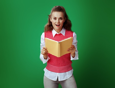 surprised modern student in grey jeans and pink sleeveless shirt holding opened yellow book against chalkboard green background. Banco de Imagens