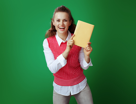 happy fit student in grey jeans and pink sleeveless shirt showing a yellow book on chalkboard green background. Good fiction book, textbook, reference educational materials Banco de Imagens