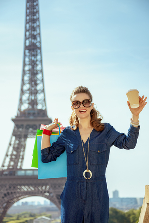 smiling elegant tourist woman in blue jeans overall with shopping bags and coffee cup not far from Eiffel tower in Paris, France. Stock Photo