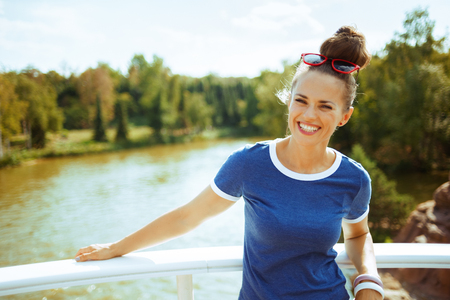 smiling modern tourist woman in blue t-shirt on river boat having river voyage.