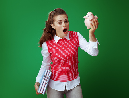 shocked modern student in grey jeans and pink sleeveless shirt with textbooks shaking pink piggy bank against green background. Financial challenges and expenditures of modern education. Stock fotó