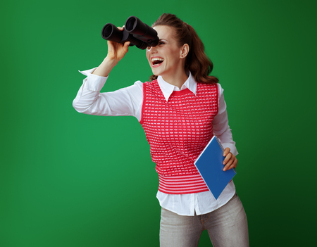 happy modern student woman in grey jeans and pink sleeveless shirt with a blue notebook looking into the distance through binoculars on green background. Consider far perspectives after degree