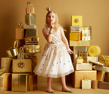 Full length portrait of modern little princess in beige fit and flare dress and a little crown on head among 2 piles of golden gifts in front of a plain wall showing shh gesture.