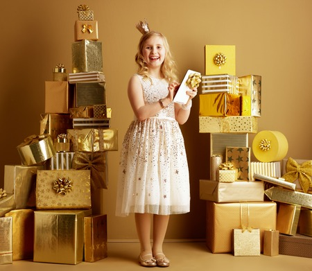 Full length portrait of happy modern little princess in beige fit and flare dress and a little crown on head using at tablet PC with bow among 2 piles of golden gifts in front of a plain wall.