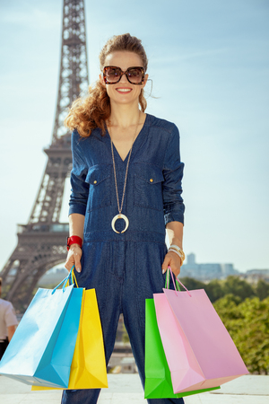 Portrait of smiling modern tourist woman in sunglasses and blue jeans overall with shopping bags in the front of Eiffel tower in Paris, France.