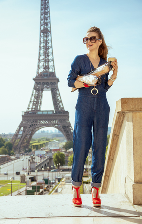 Full length portrait of smiling modern woman in blue jeans overall with coffee cup and two baguettes looking into the distance at Trocadero overlooking Eiffel tower in Paris, France.
