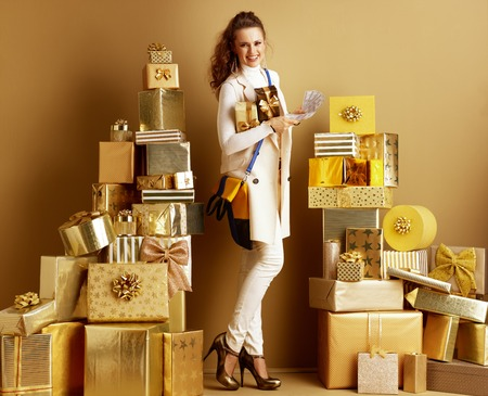 Full length portrait of happy modern woman in white clothes with present boxes with cash among 2 piles of golden gifts in front of a plain wall. Cashback deals concept. unique birthday gifts.