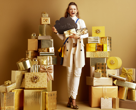 Full length portrait of smiling stylish fashion-monger in white clothes among 2 piles of golden gifts in front of a plain wall showing present boxes and CashBack sign. Cashback this Holiday Season. 写真素材