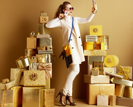 Happy elegant woman in white clothes taking selfie with phone while wearing sunglasses with price tag with qr code among 2 piles of golden gifts in. User generated content shared on social media.