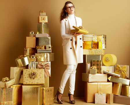 Full length portrait of unhappy young fashion-monger in white clothes with opened golden present box with a bow among 2 piles of golden gifts in front of plain wall. Dont be a bad gift giver concept.