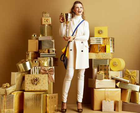 Full length portrait of smiling trendy fashion-monger in white clothes with golden goblet among 2 piles of golden gifts in front of a plain wall. Best shopping experience winner.