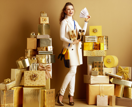Full length portrait of happy modern fashion-monger in white clothes with present boxes fanning herself with money among 2 piles of golden gifts in front of a plain wall. Cashback this Holiday Season. 写真素材