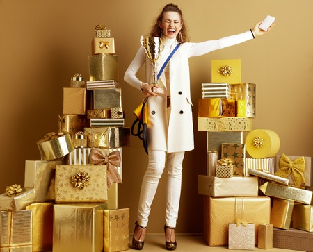 Full length portrait of happy stylish shopper woman in white clothes with smartphone and golden goblet rejoicing among 2 piles of golden gifts. win prize in the brand promotion on social networks. Stock Photo