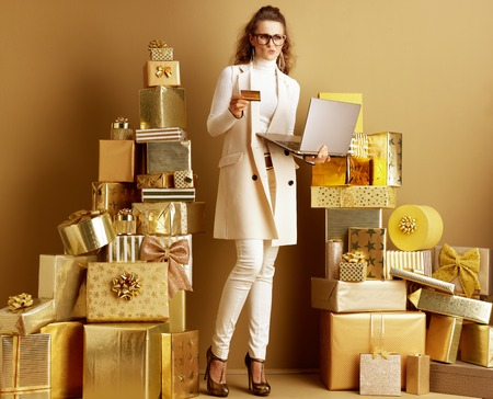 Pensive stylish shopper woman in white clothes with golden laptop and credit card making online shopping among 2 piles of golden gifts. Security is a must for modern payment systems.