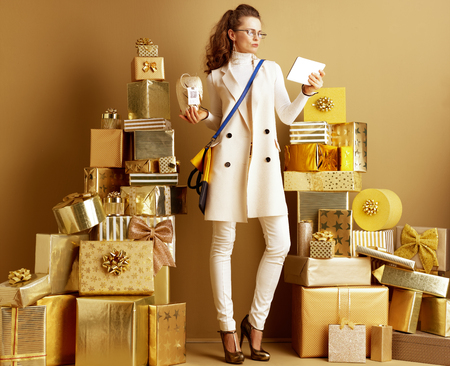 Full length portrait of stylish woman in white clothes holding product with price tag with qr code and looking at tablet PC reading review among 2 piles of golden gifts. using shopping advisor app. Stock Photo