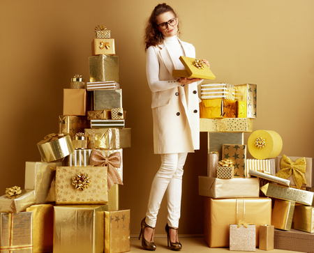 Full length portrait of unhappy stylish fashion-monger in white clothes with opened golden present box with a bow among 2 piles of golden gifts in front of a plain wall. bad gift concept.