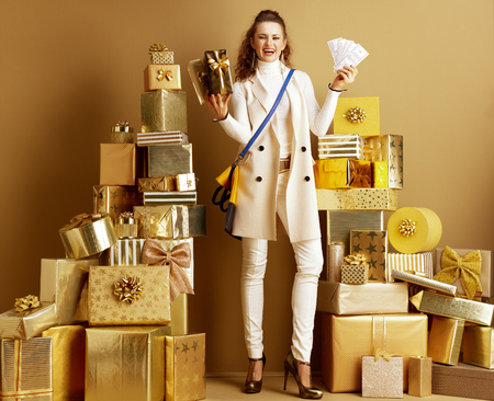Full length portrait of smiling young fashion-monger in white clothes with present boxes showing money among 2 piles of golden gifts in front of a plain wall. Cashback this Holiday Season.