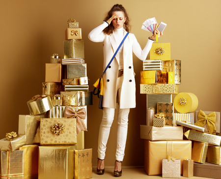 Stressed shopper woman in white clothes overwhelmed with modern pay methods holding money, credit card, bracelet and smartphone among 2 piles of golden gifts. overwhelmed with modern payment methods.