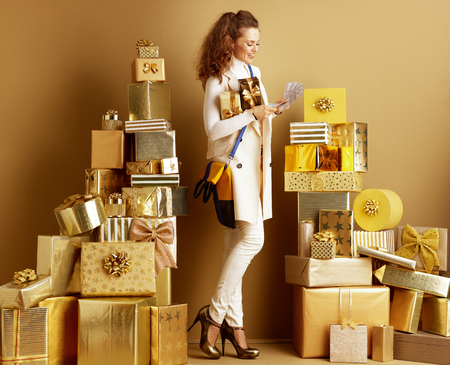 Full length portrait of happy stylish shopper woman in white clothes with present boxes counting cash among 2 piles of golden gifts in front of a plain wall. Cashback this Holiday Season.