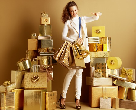 Full length portrait of happy modern woman in white clothes among 2 piles of golden gifts in front of a plain wall showing thumbs up or using fingertips as modern payment method. efficient payment. Stock Photo