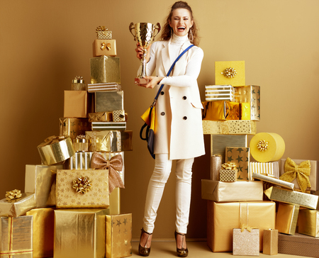 Full length portrait of smiling modern fashion-monger in white clothes among 2 piles of golden gifts in front of a plain wall showing golden goblet. win prize in the brand promotion on social networks. Stock Photo