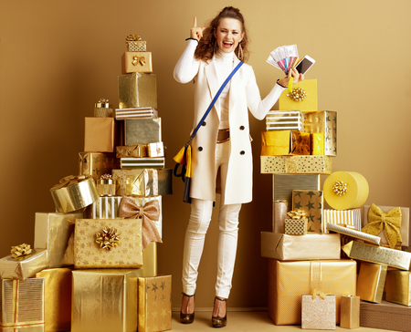 Modern woman in white clothes among 2 piles of golden gifts in front of a plain wall holding money, credit card, bracelet and smartphone got idea on modern payment methods. efficient payment.