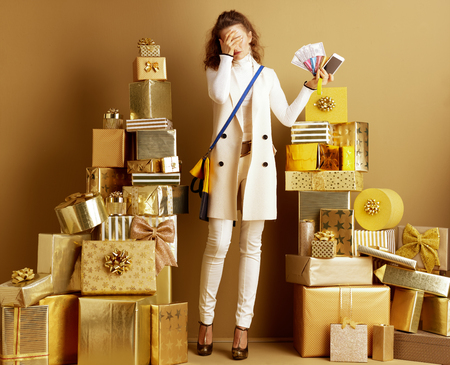 Stressed elegant woman in white clothes overwhelmed with modern pay methods holding money, credit card, bracelet and smartphone among 2 piles of golden gifts. overwhelmed with modern payment methods. Фото со стока