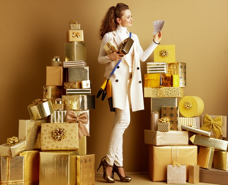 Full length portrait of happy elegant woman in white clothes with present boxes looking at money among 2 piles of golden gifts in front of a plain wall. Cashback deals concept. birthday illustration. Stock Photo