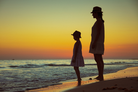 Full length portrait of active mother and child on the beach at sunset spending time. Foto de archivo - 118854278