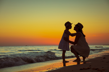 healthy mother and child tourists on the ocean shore at sunset kissing. Foto de archivo - 118854281