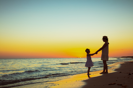 Full length portrait of active mother and daughter on the ocean shore at sunset having fun time. Banco de Imagens