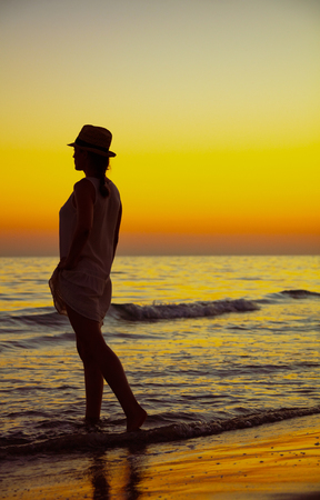 Full length portrait of fit woman on the ocean coast enjoying sunset.