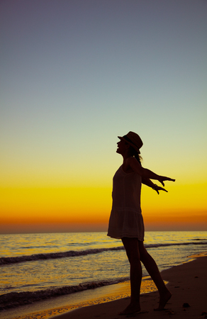 Full length portrait of young woman on the seashore at sunset rejoicing.