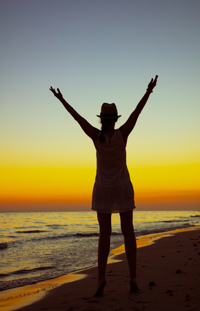 Full length portrait of healthy tourist woman on the ocean coast at sunset rejoicing.