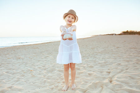 Full length portrait of smiling fit tourist girl in white dress and hat on the ocean shore in the evening showing amazing find as she thinks.