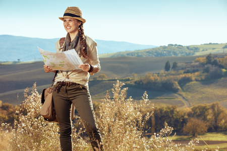 happy active tourist woman in hiking clothes with bag with map looking into the distance on summer Tuscany trekking. 版權商用圖片