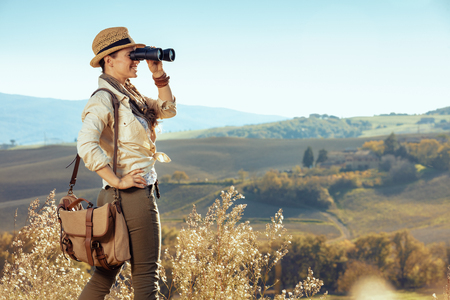 smiling young traveller woman in hiking clothes with bag in Tuscany ,Italy looking into the distance through binoculars.
