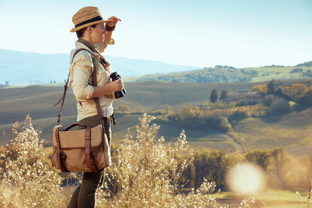 pensive fit woman hiker in hiking gear with bag with binoculars looking into the distance. summer hiking in Tuscany ,Italy. 版權商用圖片