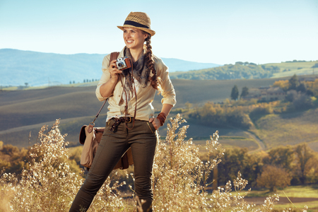 happy adventure solo tourist woman in hiking clothes with bag and retro film photo camera looking into the distance on summer Tuscany trekking. 版權商用圖片