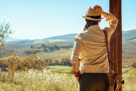 Seen from behind healthy solo tourist woman in hiking gear with bag summer hiking in Tuscany ,Italy and looking into the distance.