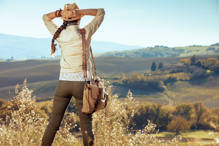 Seen from behind active tourist woman in hiking clothes with bag against scenery of summer Tuscany ,Italy looking into the distance.