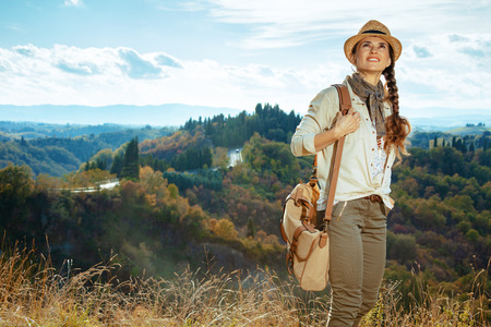 smiling fit traveller woman in hiking clothes with bag on summer Tuscany trekking looking into the distance. 版權商用圖片