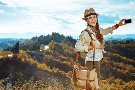 happy healthy solo traveller woman in hiking clothes with bag taking photo with phone in the front of scenery of summer Tuscany ,Italy. 版權商用圖片