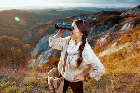 smiling healthy woman hiker in hiking clothes with bag in Tuscany ,Italy looking into the distance through binoculars. Imagens