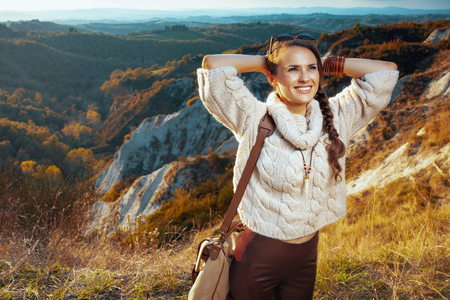 relaxed young traveller woman in hiking clothes with bag enjoying summer Tuscany view enjoying promenade. Stock fotó