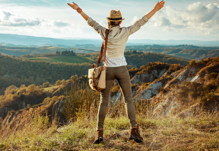 Full length portrait of happy active solo traveller woman in hiking gear with bag rejoicing against scenery of summer Tuscany ,Italy. Banco de Imagens